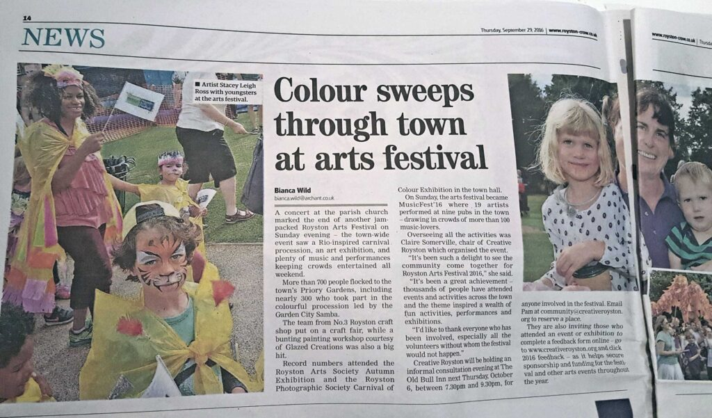 Royston Crow article about Royston Arts Festival Carnival-like parade showing image of by Leigh artist, Stacey Leigh Ross, surrounded by children who made capes as part of her Carnival craft workshops for Royston Museum. The costumed children were then part of the Carnival - like parade hosted for the Royston Arts Festival 2016yston Museum
