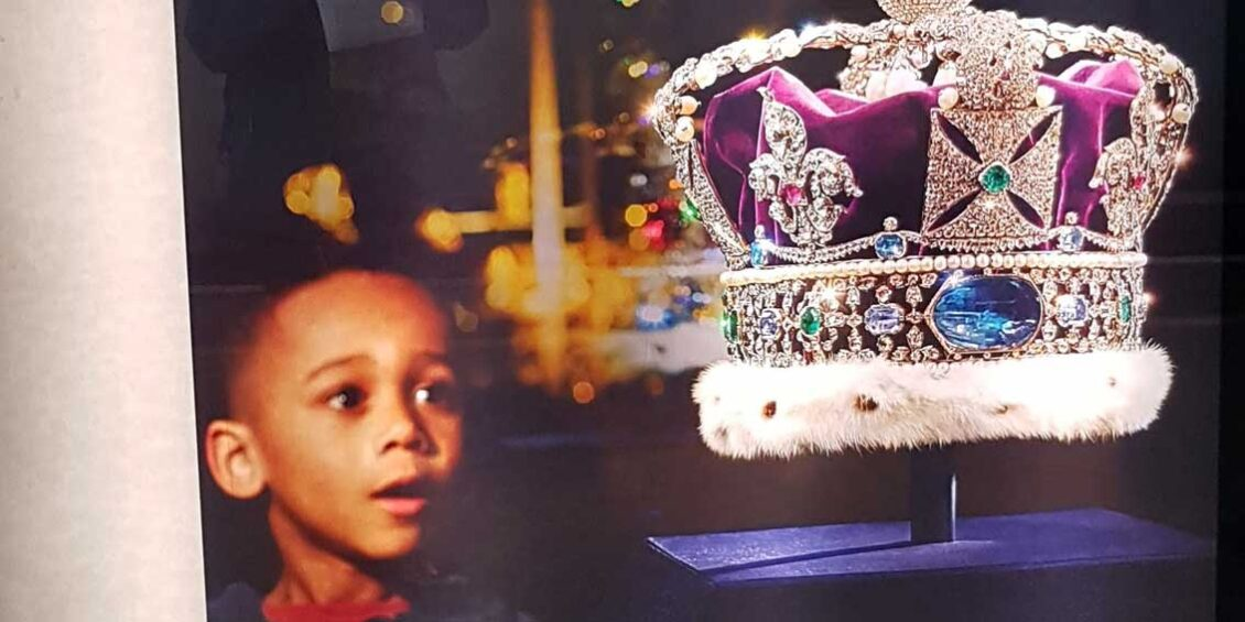 Cropped photo of a billboard at St Pancras in 2019 showing a black boy gazing longingly at the crown jewels