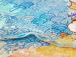 water and waves drawn in a Japanese style with a fish off to the right and lots of textured elements to the bttom of the painting representing waves washing up on a pebbly beige textured shore that sparkles with hints of gold leaf