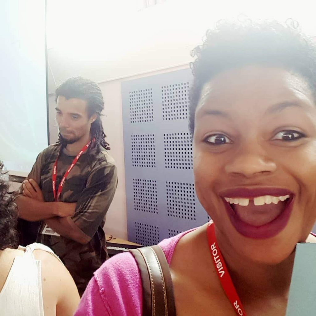 Artist Stacey Leigh Ross grinning like a loon with Akala in the background