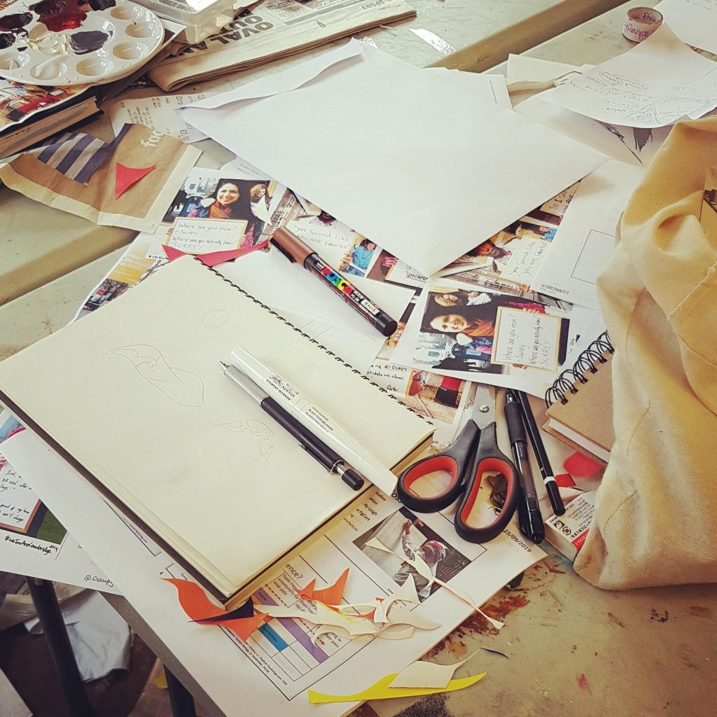Messy desk as students cut up pages to create posters