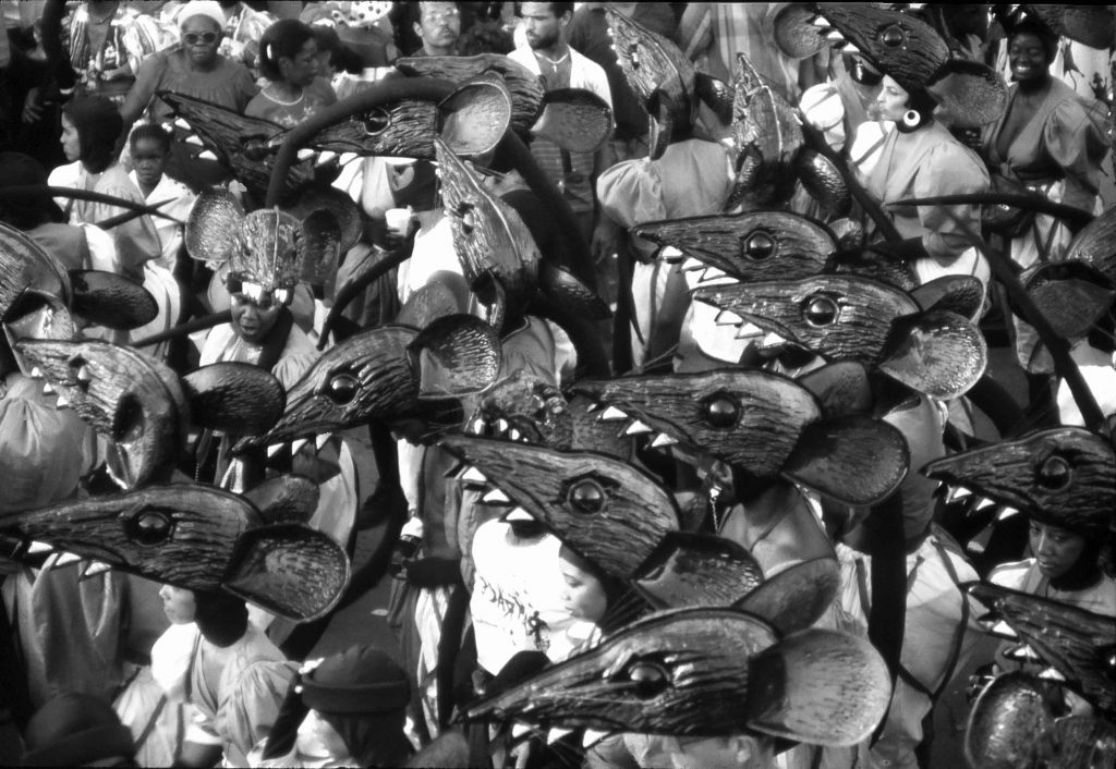 Photo of people in carnival costumes with plastic moulded rat heads for head pieces. All together they look like a horde of rats dancing down the street