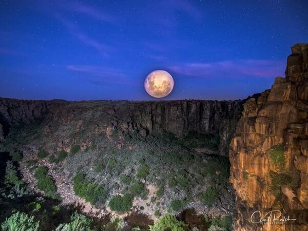 The moon in the night sky above the canyon at Tiger Canyon Private Game Reserve