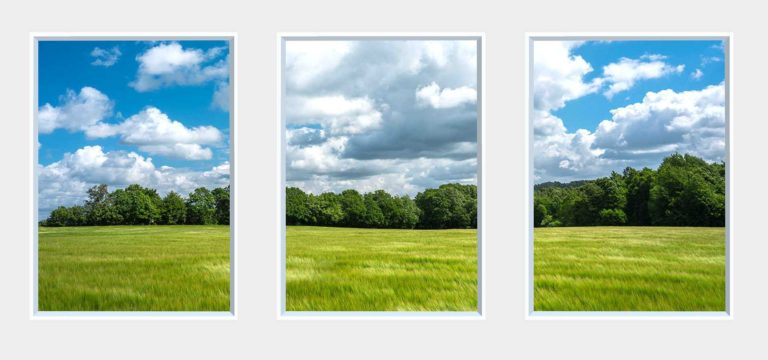 3 panel landscape window with green field under cloudy blue sky