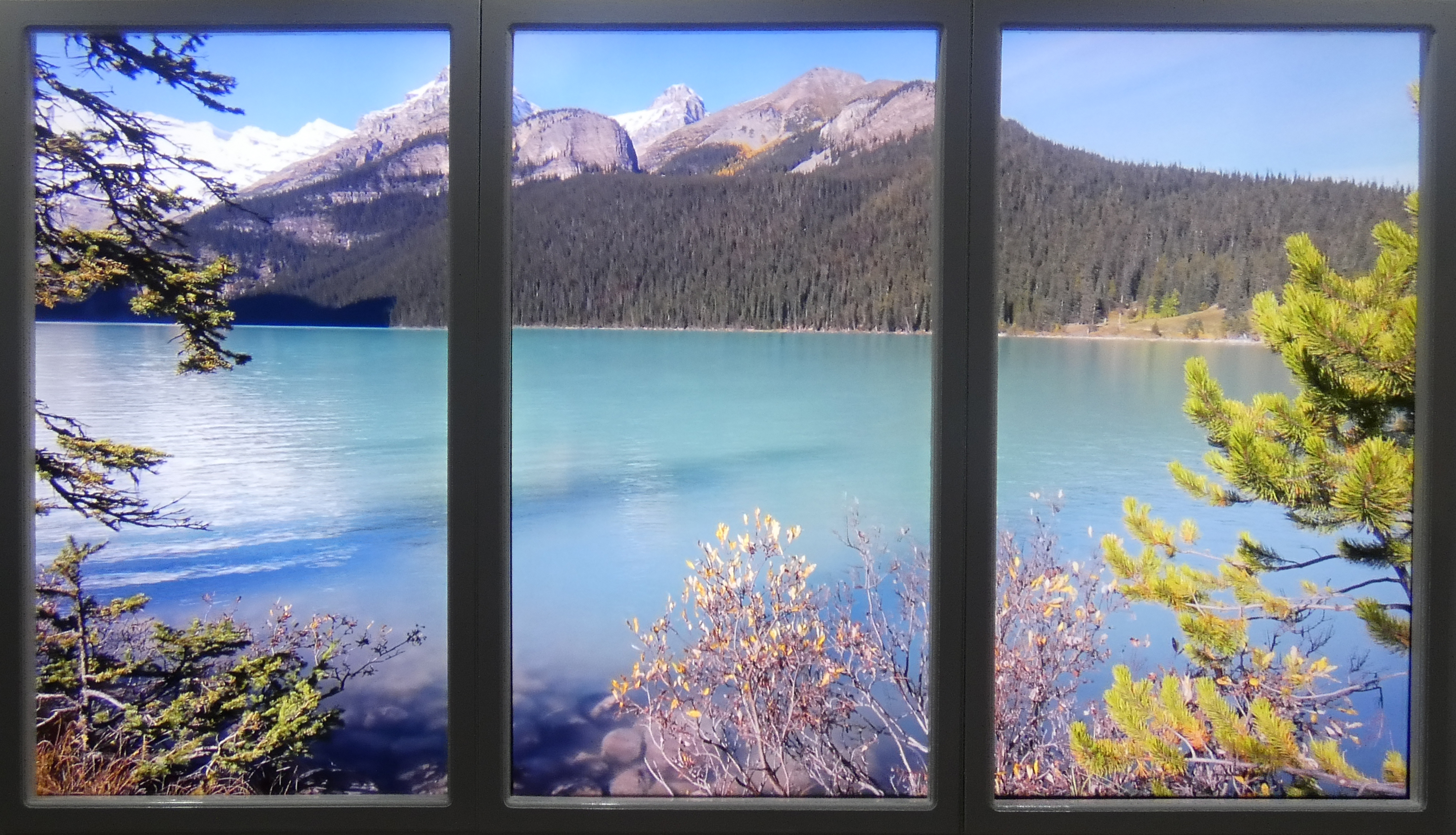 Three windows showing view of lake and mountains