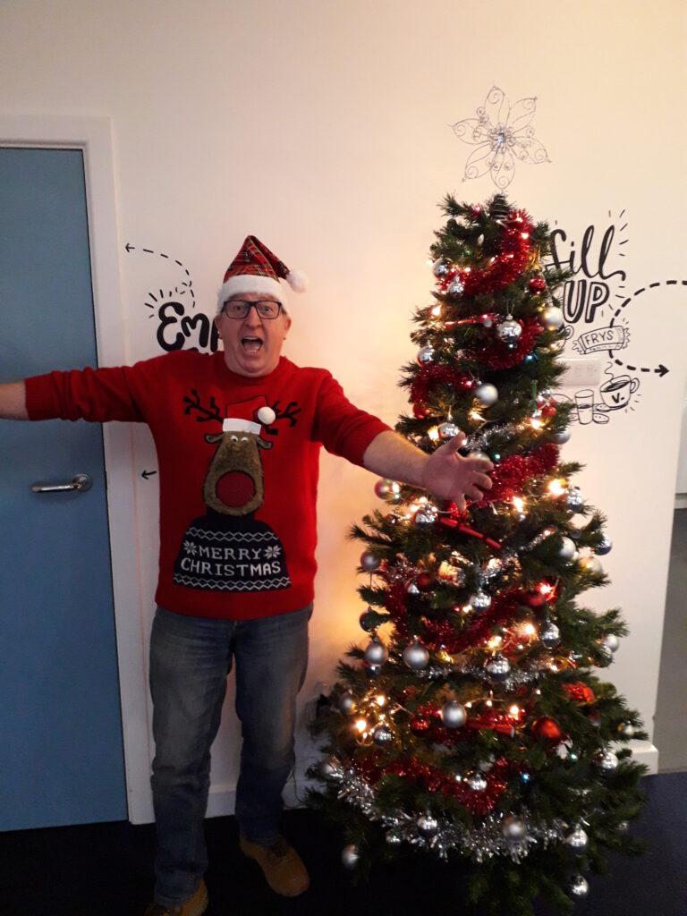 Sky Inside owner Allan wishing Merry Christmas by festive tree