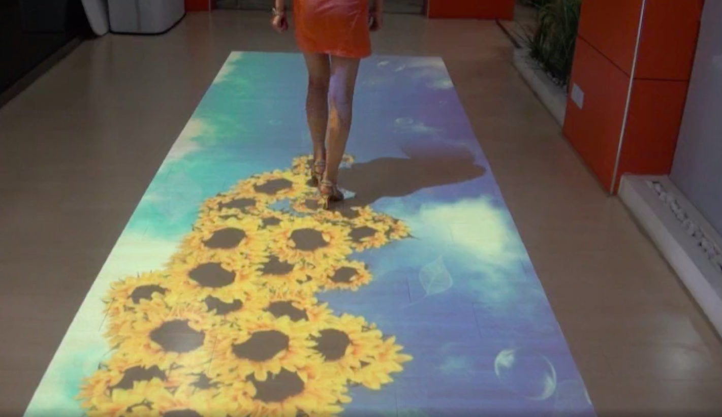 Woman walking along interactive floor with sunflowers