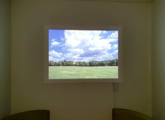 Luminous backlit fake window with green field and blue cloudy sky image