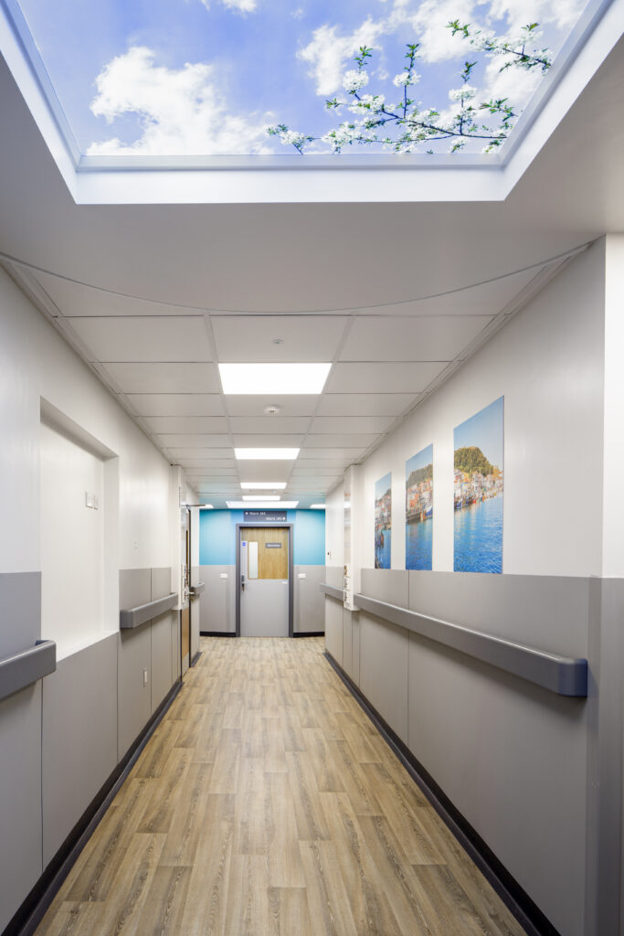 Long hospital corridor brightened with fake ceiling window of blue sky, clouds and blossom