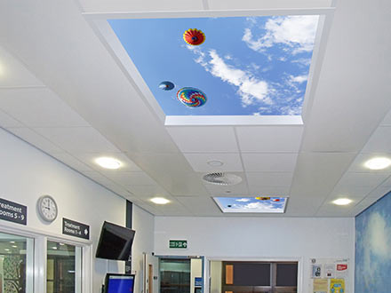 Hospital room with fake windows featuring blue skies and hot air balloons