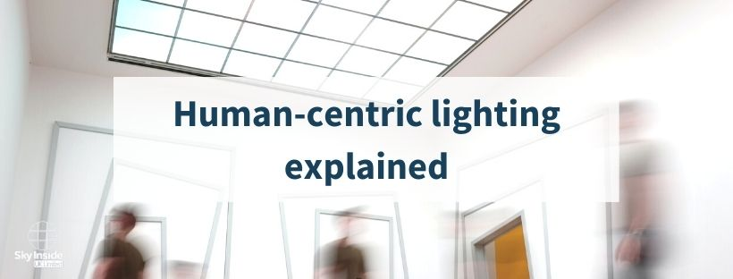 Bright room with large, panelled skylight and blurred people walking underneath. Blog post banner saying 'human-centric lighting explained'