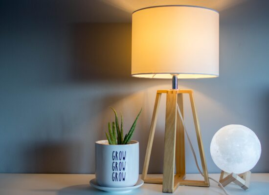 Warm light lamp by grey wall on a table with small plant and moon sphere decoration