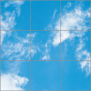 Artificial skylight for uk with nine panels in a square showing bright, light blue sky and wispy white clouds