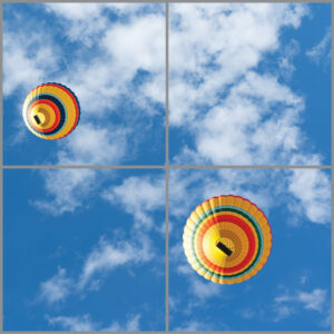 4-panel window with blue skies, white clouds and two multi-coloured hot air balloons