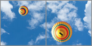 2-panel window with blue skies, white clouds and two multi-coloured hot air balloons
