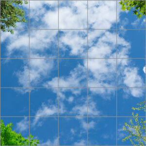 25-panel window with blue skies, white clouds with different types of green leaves on branches in each corner