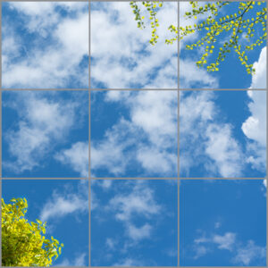 9-panel window with blue skies, white clouds and twigs with yellow-green leaves