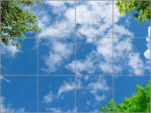 12-panel window with blue skies, white clouds and trees in three corners with green leaves