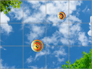 12-panel window with blue skies, white clouds, green leaves and colourful hot air balloons