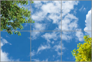 6-panel window with blue skies, white clouds and green and yellow leaves, worm's eye view