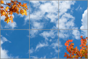 6-panel window with blue skies, white clouds and branches with autumnal leaves