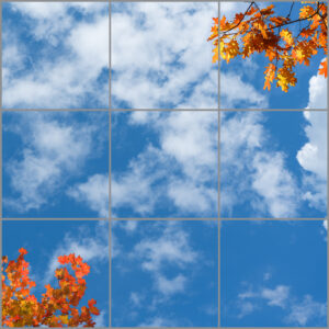 9-panel window with blue skies, white clouds and orange, red and yellow autumn leaves