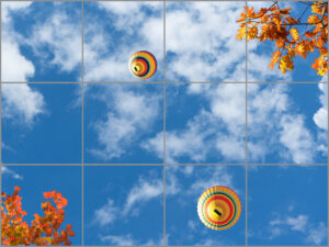 12-panel window with blue skies, white clouds, twigs with orange and yellow leaves and two multi-coloured hot air balloons