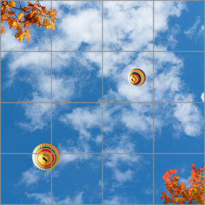 Worm's eye view of a 9-panel window with blue skies, white clouds, autumnal coloured leaves and hot air balloons