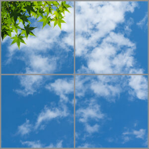 4-panel window with blue skies, white clouds and green leaves