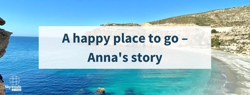 Blog banner with text 'A happy place to go - Anna's story' in white box in front of bright blue sea cove image