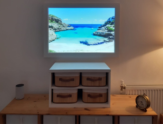 Artificial window showing beach scene in bedroom above table and chest of drawers