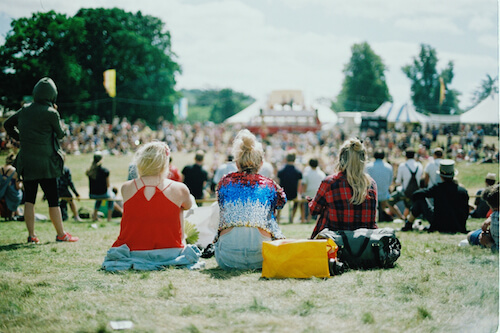 Three blonde girls sitting on grass at a music festival.