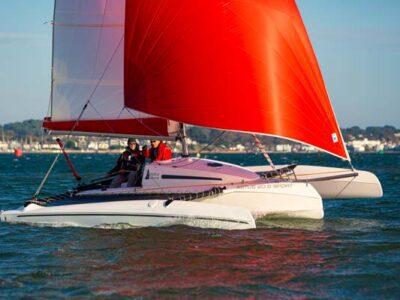 Astus 20.5 with kite raised in Poole Harbour