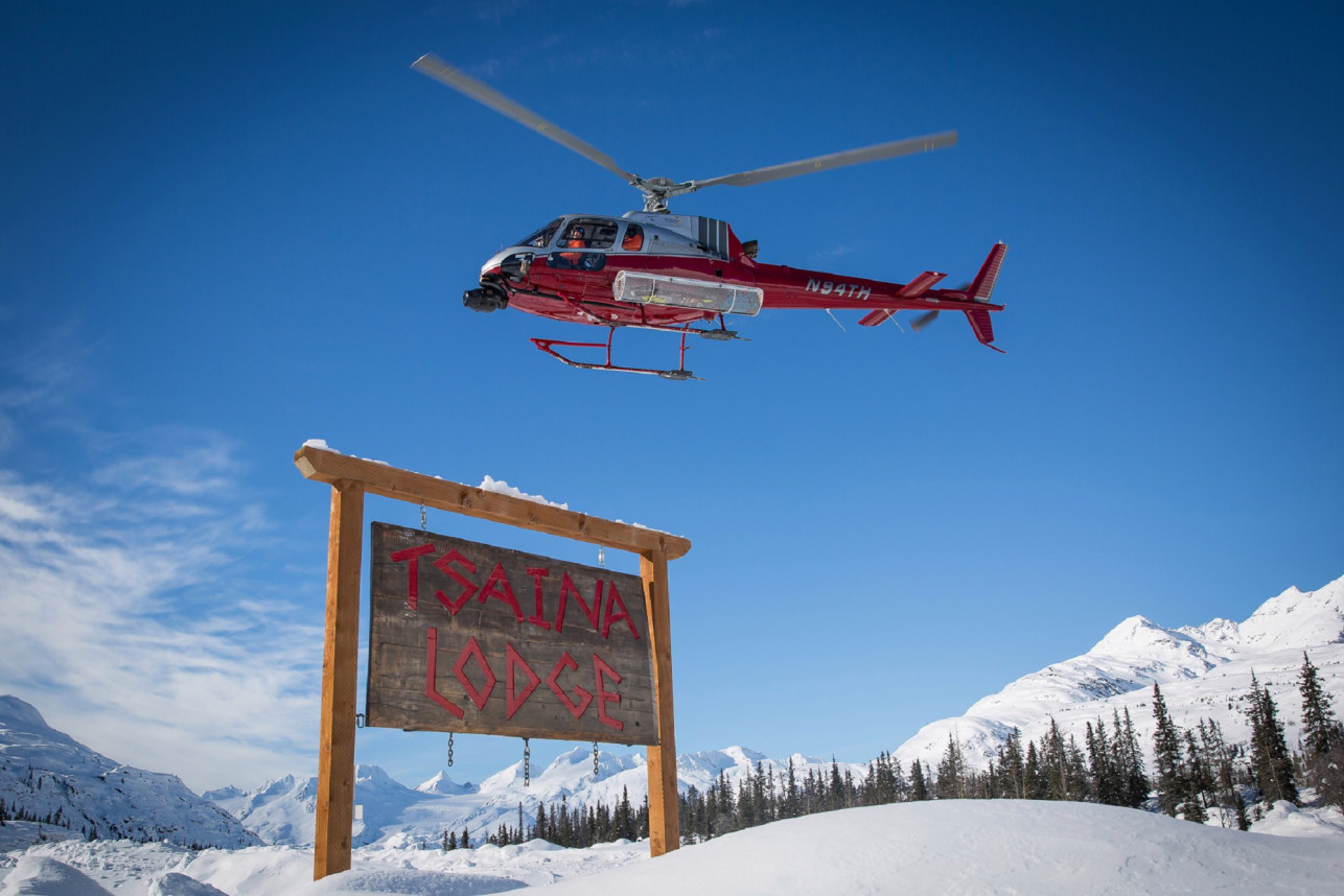 Valdez Heli Ski Guides red helicopter flying in the air over Tsaina Lodge wooden signe near Thompson Pass in the Chugach Mountains of Alaska