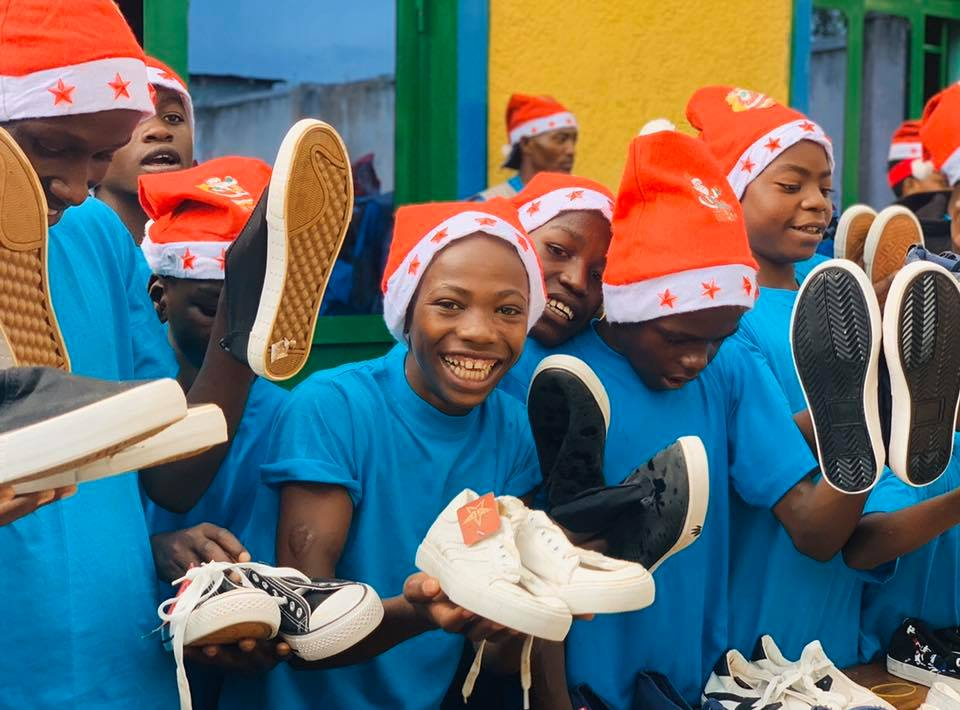 Street kids with Santa hats on, holding some new shoes