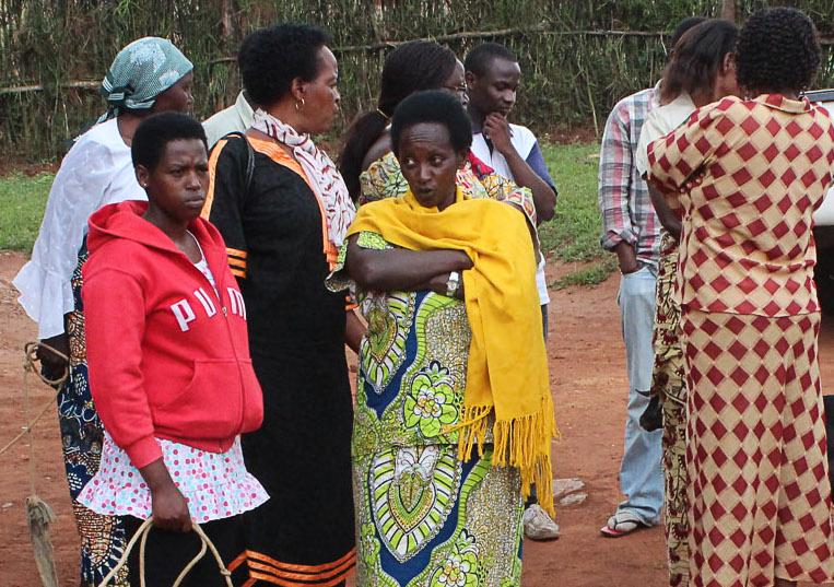 Group of people stood around talking.