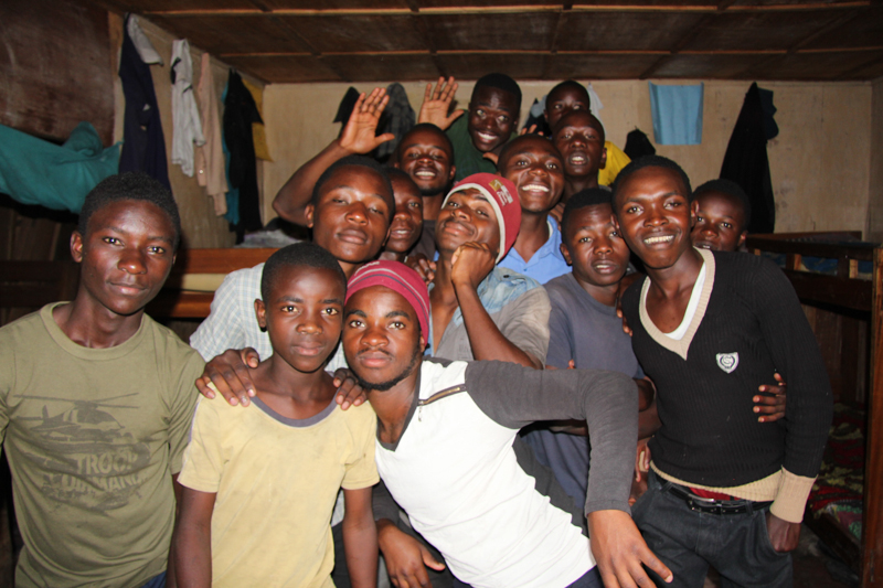Group of young men hugging, waving and smiling.