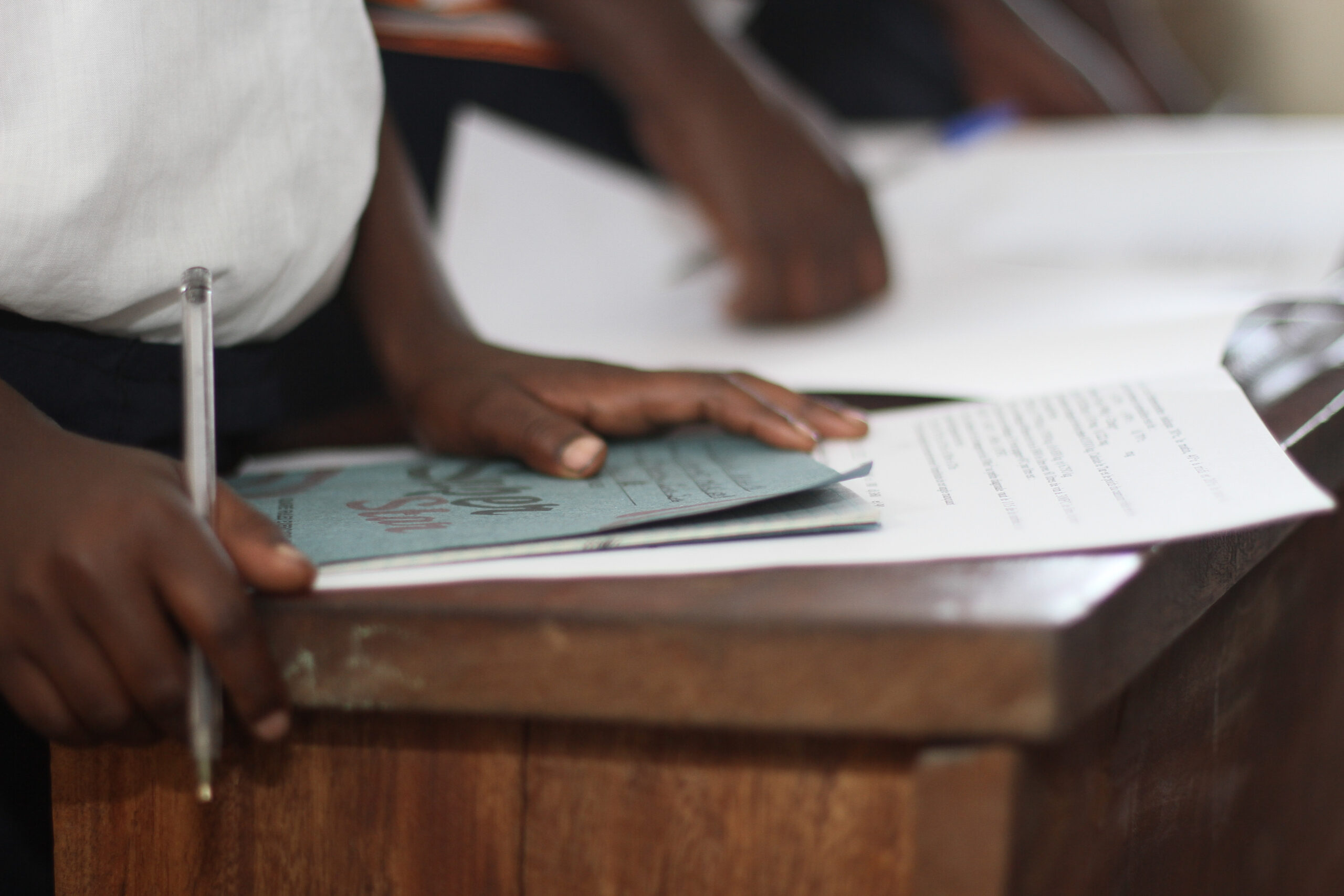 A book on a wooden desk. The child is holding a pen over the book