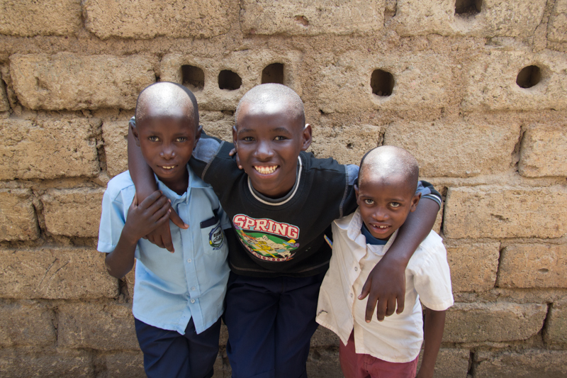 Three young boys smiling with their arms around each other.