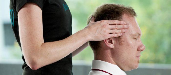 Massage therapist / Masseuse massaging man's head in an office