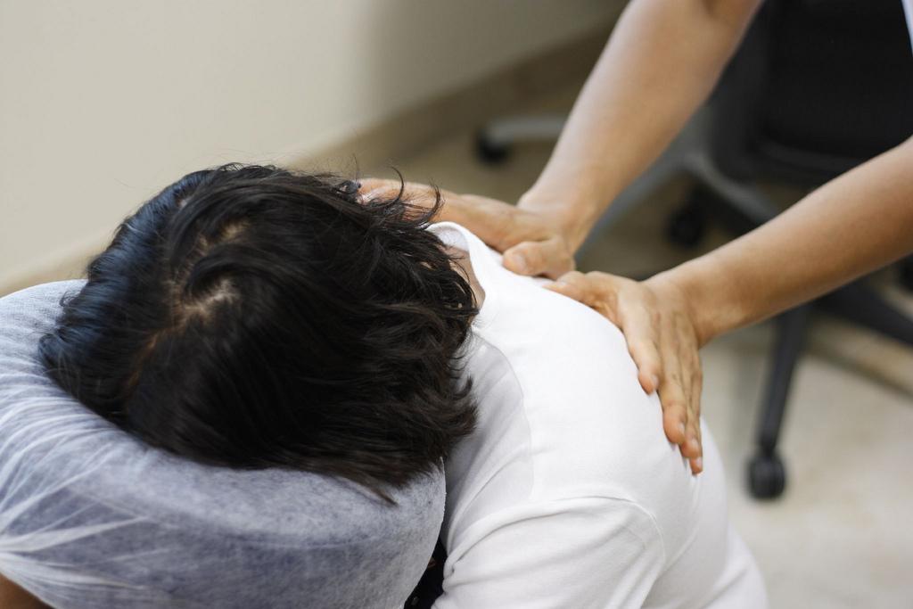 Woman in massage chair receiving a shoulder massage
