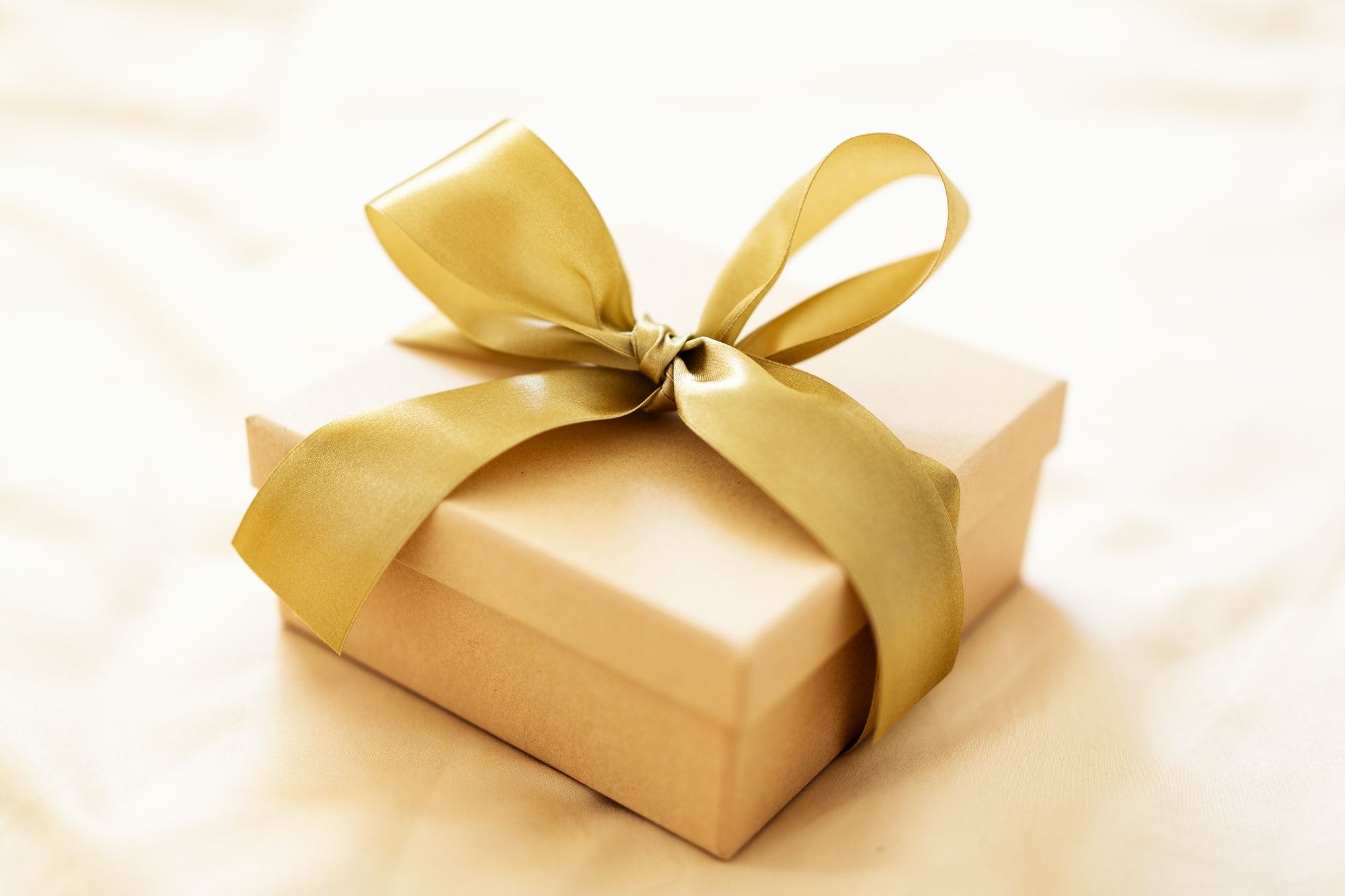 Gift with golden ribbon on golden background