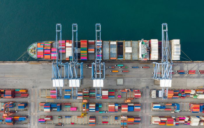 A birds eye view / drone view / aerial view of a port showing a container ship being loaded with multicoloured containers