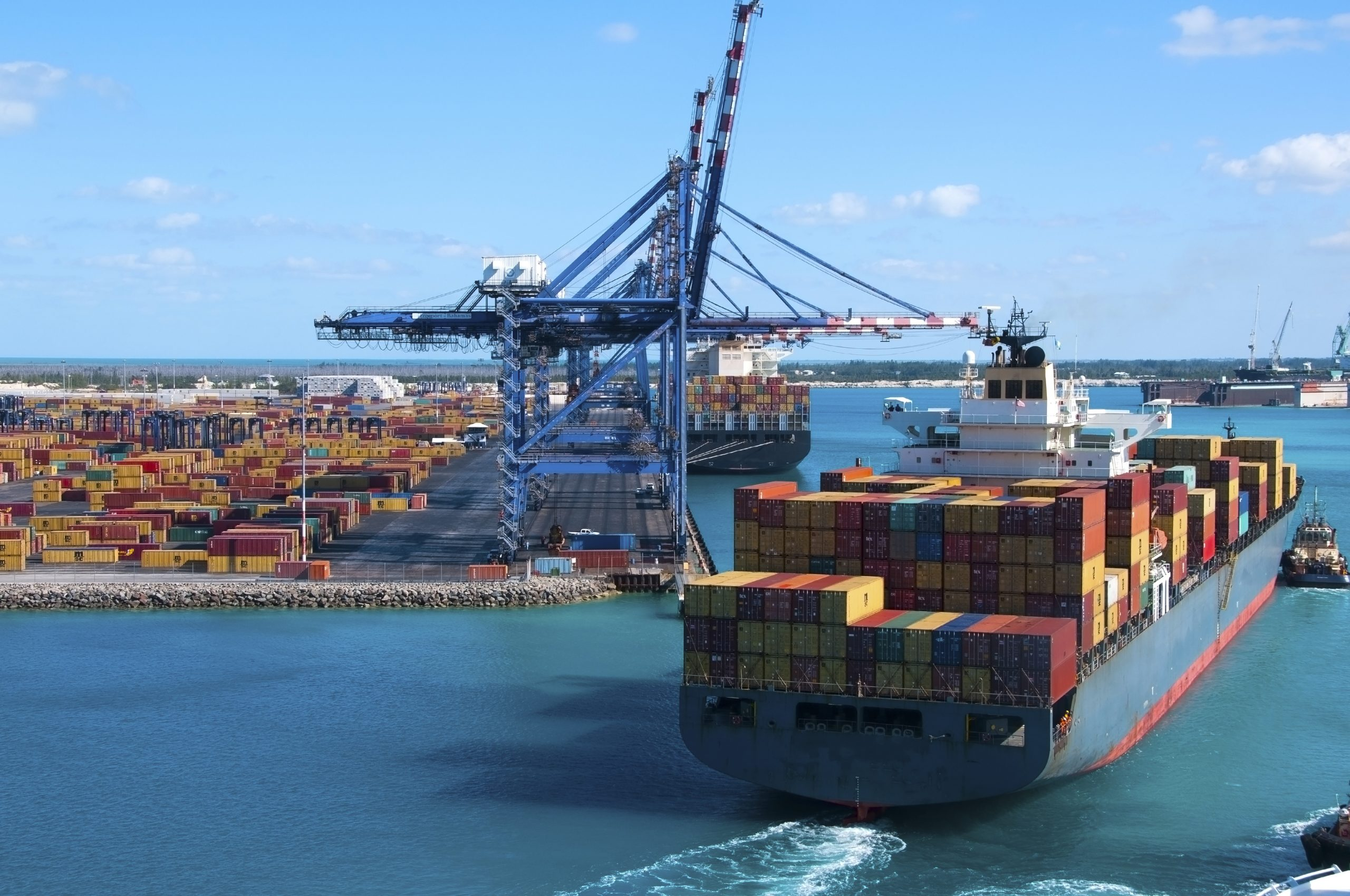 A large container ship sailing into a port with a tug boat next to it