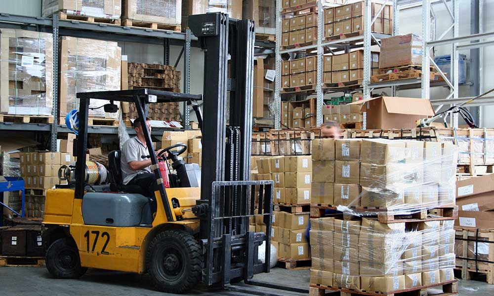 Road Freight - Busy warehouse with pallet trucks working