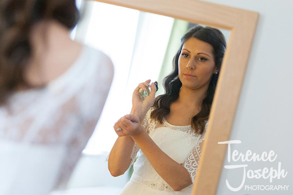 Bride putting on perfume at Oakwood House in Maidstone