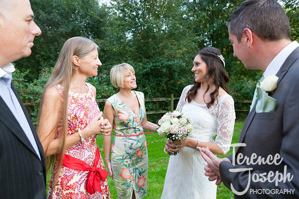Group chatting outside in the garden at The Plough at Leigh wedding reception