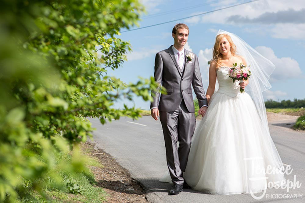 bride and groom photos walking down the road hand in hand