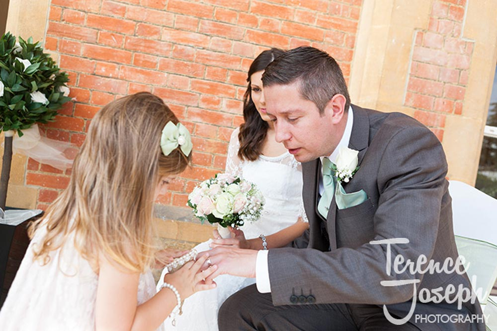Little girl looks at groom's ring at Oakwood House in Maidstone