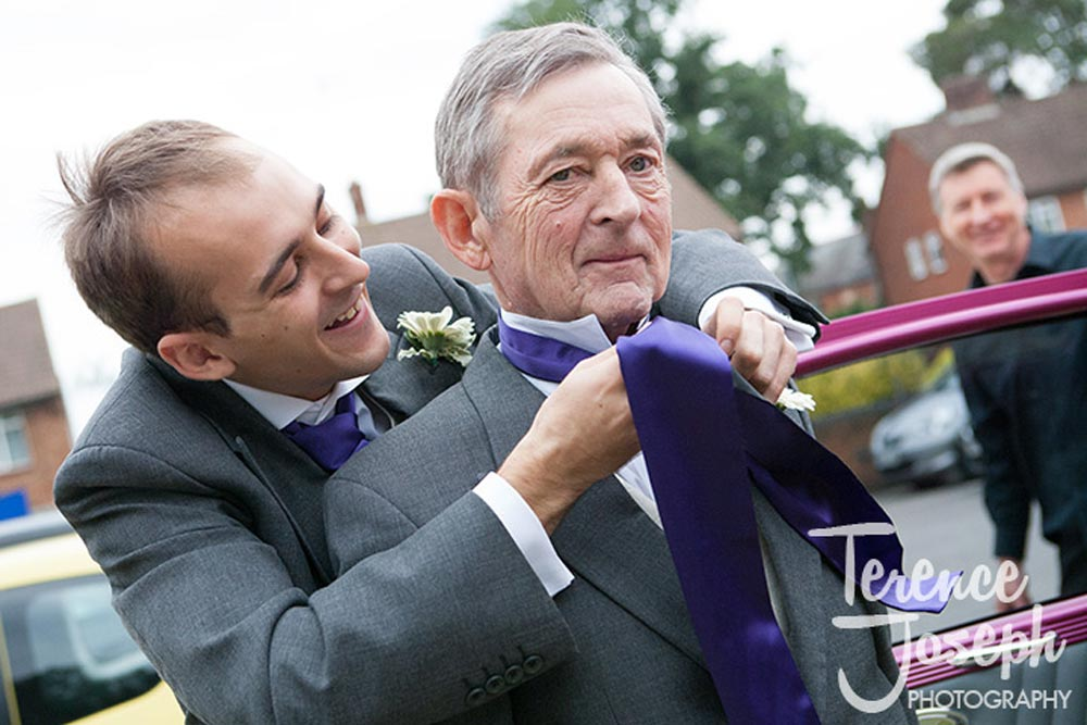 Father of bride is having a tie tied